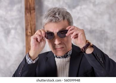 Portrait of a man in black jacket dresses glasses
