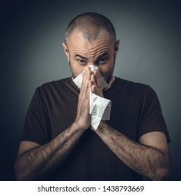 portrait of a man blowing his nose with a tissue. look at the camera. concept of malaise and allergy.