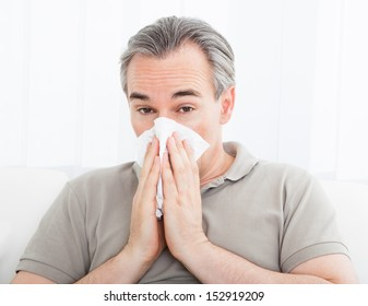 Portrait of a man blowing his nose