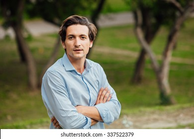 portrait of a man in blue shirt standing outside in park