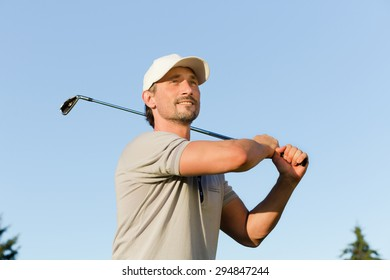 Portrait of man with brassie isolated on blue background. Mature golfer on taking a swing in the fairway on golf course.