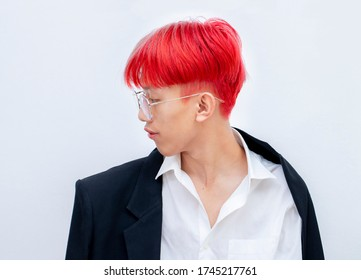 Portrait of a man with bright colored flying hair, all shades of red,purple. Hair coloring.Hair fluttering in the wind. Teen age with short hair. Professional coloring.