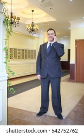 Portrait of a man in a business suit and tie with phone in a lobby of luxury apartment building