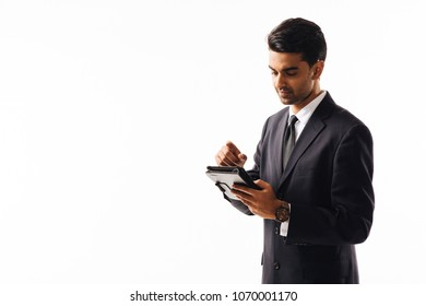 Portrait of a man in business suit writing on an electronic pad, isolated on white background
