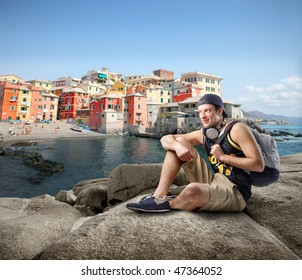 Portrait of a man in casual clothes sitting on a rock looking over a seascape and a typical village of the northern Italy coast