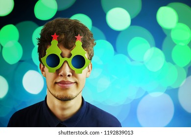 Portrait of a man in Christmas glasses. Portrait of cheerful, attractive man on blue sparkles background with copy space for text, look over glasses make wide smile. Copyspace for text