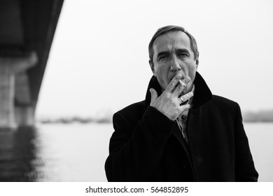 Portrait of a man with a cigarette standing under the bridge