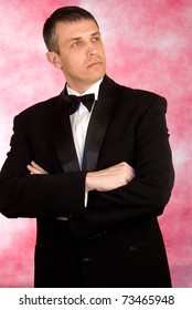 Portrait the man in a classical tuxedo on an pink  background