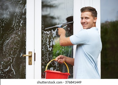 Portrait Of Man Cleaning House Windows