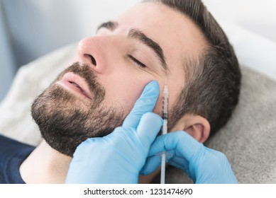 Portrait of man at clinic doing face fillers, injection procedure.