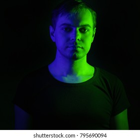 Portrait of a man with colored light and dark background.