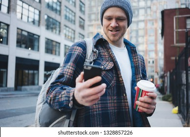 Portrait of man with cup of coffee and using mobile phone in the city
