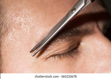 Portrait of man cutting eyebrow hairs.