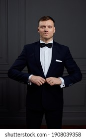 portrait of a man in a dark blue tuxedo and white shirt