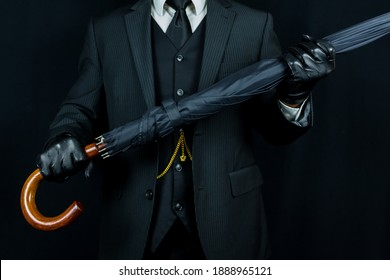 Portrait of Man in Dark Suit and Leather Gloves Holding Umbrella Like a Rifle on Black Background. Classic British Gentleman. Vintage Style and Elegance. Vintage Style. Retro Fashion.