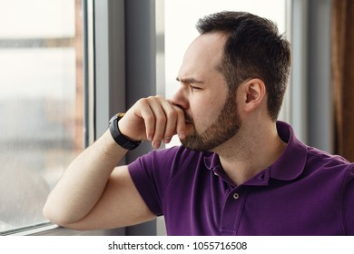 Portrait of a man in despair, misery or sorrow leaning against a window