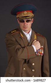 Portrait of a man dressed in a military uniform, with his fist on his chest.