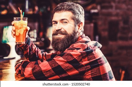 Portrait man, drinking orange juice. Barman in pub or restaurant. Cheerful bearded man, drink cocktails and smile. Tropical alcoholic fresh cocktail. Bearded man cocktail.