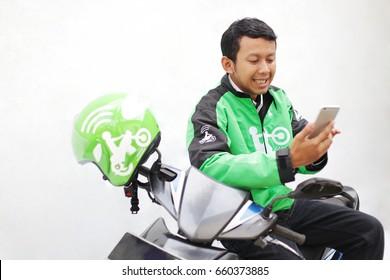 portrait man driver transportation motorcycle gojek, grab, uber touch mobile for order