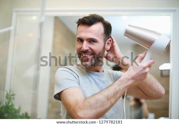Portrait of man drying his hair in bathroom