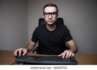 Portrait of man in eyeglasses working on pc
