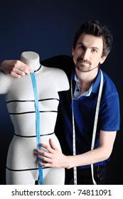 Portrait of a man fashion designer working with dummy at studio.