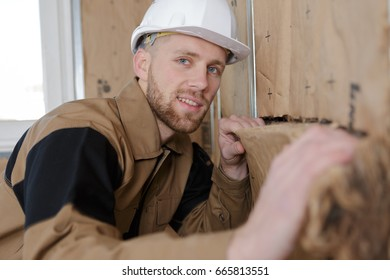 portrait of man fitting insulation into walls