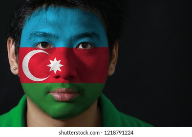 Portrait of a man with the flag of the Azerbaijan painted on his face on black background, blue red and green with a white crescent and big star.