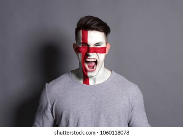 Portrait of man with the flag of England painted on his face. Football or soccer team fan, sport event, faceart and patriotism concept. Studio shot at white background, copy space