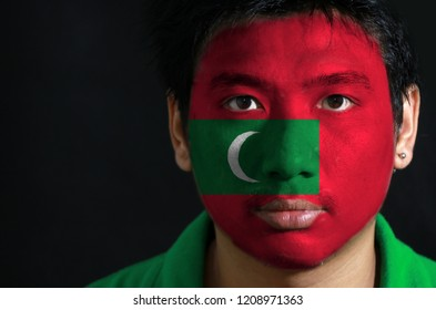 Portrait of a man with the flag of the Maldives painted on his face on black background. green with red border and white crescent on center.