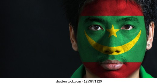 Portrait of a man with the flag of the Mauritania painted on his face on black background. The concept of sport or nationalism. two red stripes flanking a green field with a golden crescent and star.