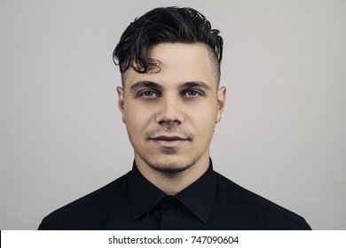Portrait  of man in formal clothing (shirt) and perfect clean skin on grey background with studion light, Illuminated portrait of handsome male model with modern hairstyle. Fashion formal portrait.