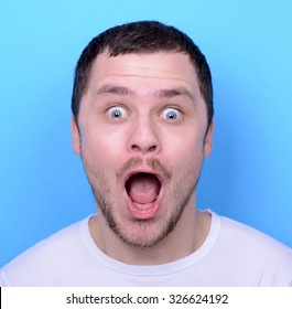 Portrait of man with funny face against blue background