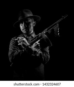 The Portrait of Man with Gangster / Mafioso / Mafia Suit and Air Soft Gun.  Isolated on Black Background Samarinda, Indonesia 15 JUNE 2019