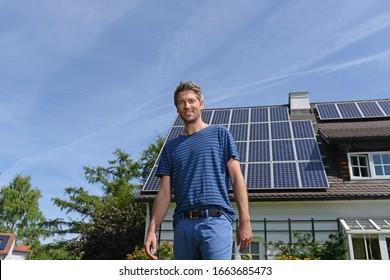 Portrait of man in garden of solar paneled house