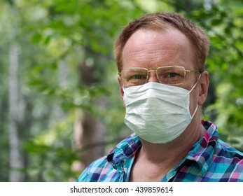 Portrait of a man with glasses and a medical mask. Background nature, a lot of greens - the grass, the trees. Concept - an allergy in the spring, summer. Summer's disease - an allergy, common cold