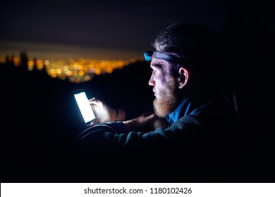 Portrait of man with glowing smartphone and led light against night sky with stars and glowing city light background.