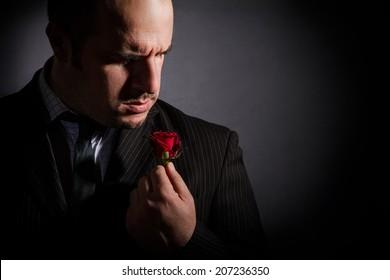 Portrait of man, godfather-like character. Studio shoot, black background.