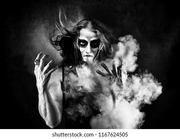 Portrait of man in goth style clothes with scull makeup. Blowing the smoke.