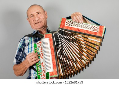 Portrait of a man, grandfather plays the accordion. On a gray background.