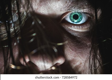 Portrait of a man with a green eye for horror or halloween.