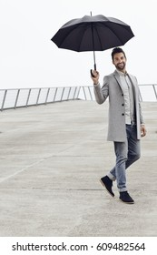 Portrait of man in grey smiling with umbrella