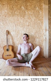 Portrait of a man with a guitar. The guy sits on the floor near the wooden wall. Acoustic guitar stands near the musician. Musical instrument. A man without a shirt.