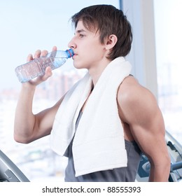Portrait of a man at the gym drinking water
