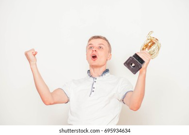 portrait of man handing gold cup up, isolated on white. Concept of leadership and success