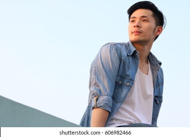 Portrait man: A handsome man is looking to a beautiful sunset, it makes him happy. Attractive men feel relaxed and determined. Cool guy wear denim jacket, vest. jeans. He looks charming. copy space