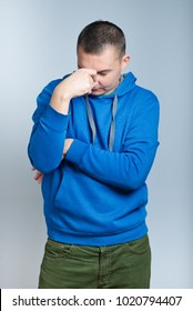 portrait of a man has the bad news and grabbed head, dressed in a blue hoodie, isolated on a gray background