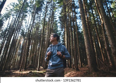 Portrait of a man hiker walking on the trail in the woods. Strong sporty traveling male with backpack on a forest background.