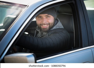 Portrait of man in his car. looking camera