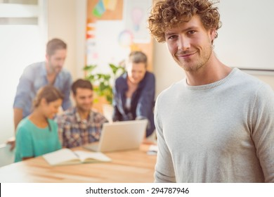 Portrait of a man with his colleague behind him in the office